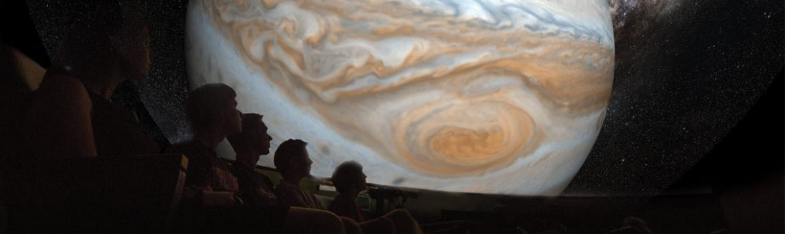 A picture of people watching a film about planets